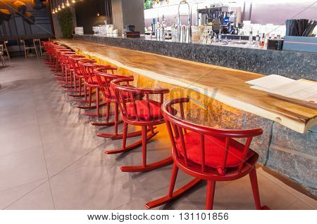 Close up of long common table near the counter with red chairs in restaurant