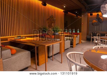 Wonderful interior of modern restaurant. Wooden tables and small couches create cozy atmosphere