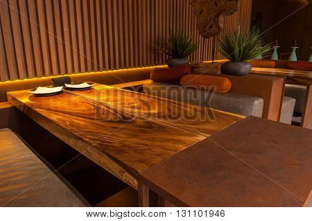 Close up of wooden table and sofa in a restaurant. Yellow lighting creates romantic effect