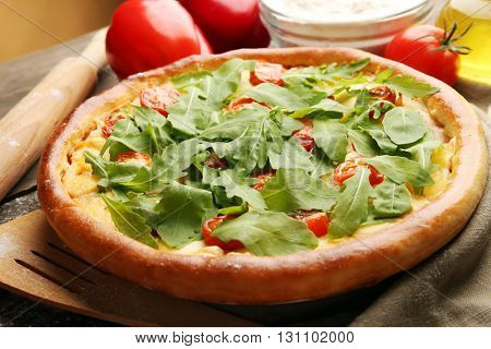 Pizza Margherita with arugula and kitchenware, close-up