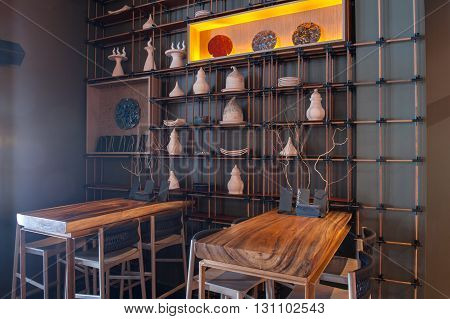 Elegant wooden tables and chairs in restaurant. Interesting utensil on the wall creates special decoration of interior
