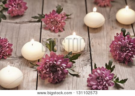 Spa theme with candles and flowers on wooden background
