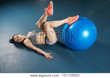 Beautiful body builder posing legs on large blue ball on the floor of the gym