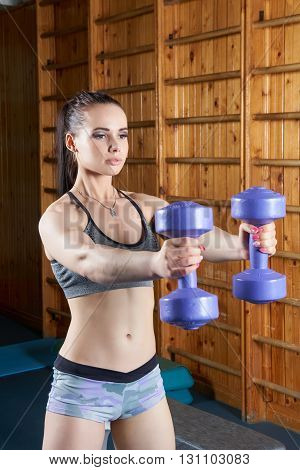 Beautiful young girl exercising with dumbbells near wall bars in the gym