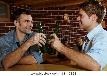 ¿Dos hombres bebiendo cerveza barra, botellas tintineantes, sonriendo, mujeres que hablan en fondo.?