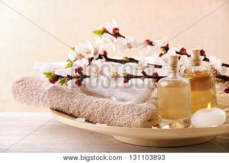 Spa composition with blooming branches in wooden bowl