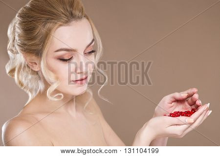 Large Portrait Of A Girl With Red Capsules In The Hands Of