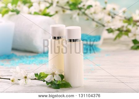 Spa composition with blooming branches on wooden table