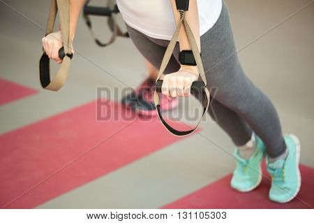 Close up of female fit body training with trx fitness straps in gym. Woman is standing and doing push ups
