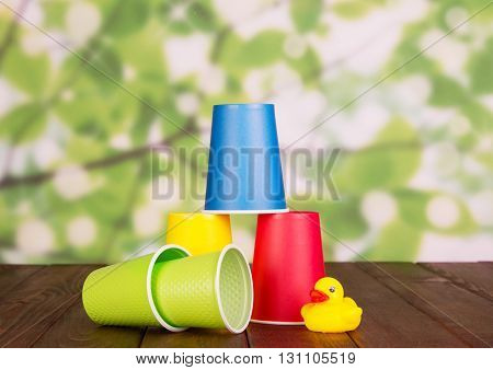 Bright disposable plastic glasses on abstract green background.