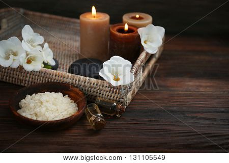 Spa set with sea salt, exotic flowers and candles on wicker tray