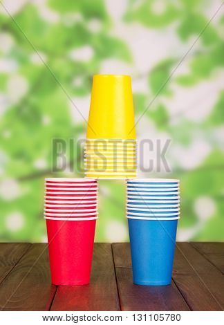 Multi-colored paper cups on abstract green background.