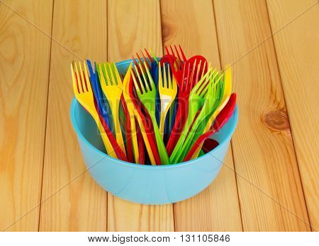 Colored plastic bowl, fork and spoon on a background of light wood.