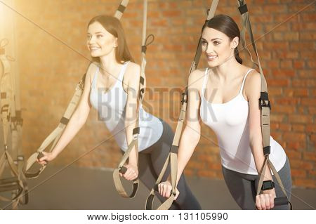 Attractive two girls are doing push-ups with trx fitness straps. They are standing and smiling. The ladies are looking forward with aspiration