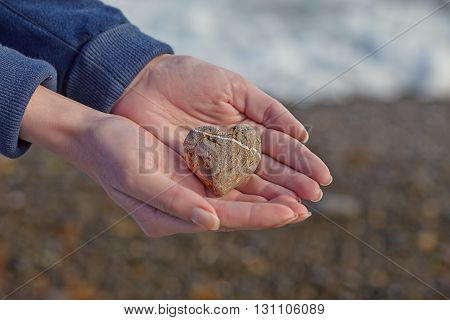 Cute stone heart in a womans hands