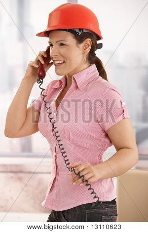 Portrait of young architect talking on landline phone in office, smiling.?