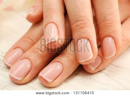 Woman hands with beautiful rose  petals on wooden background, close up
