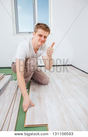 Carpenter installing light laminate flooring in a room and showing a thumb up