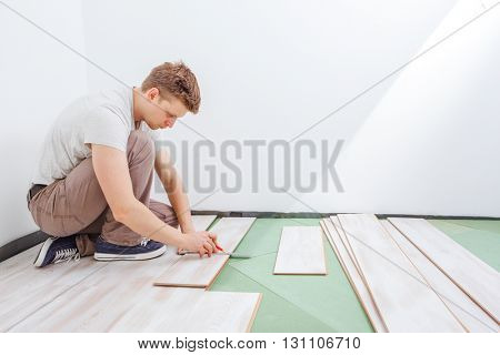 Handyman using a speed square to cut a  laminate plank in order to install new flooring