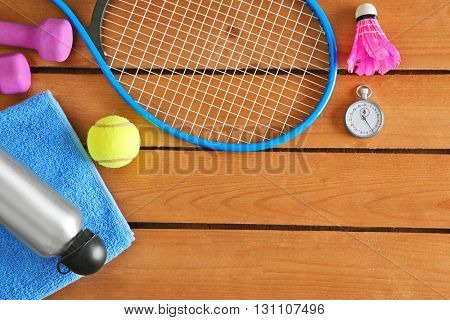 Sport equipment with bottle of water on wooden background