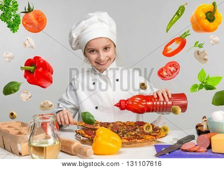 little girl pour pizza with ketchup on kitchen table with flying food ingregients
