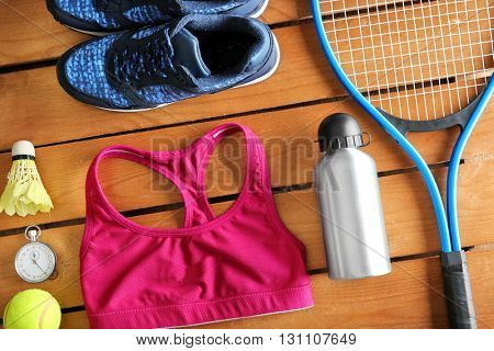 Sport equipment and clothes on wooden background