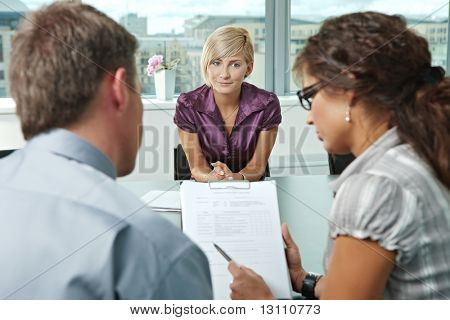 Attractive woman applicant hoping in good results after job interview. Over the shoulder view.