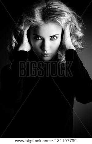 Black-and-white portrait of a calm beautiful young woman looking at camera. Emotions. Beauty, fashion.
