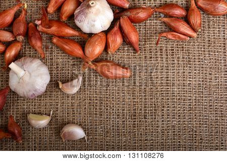 Background with garlic. Garlic on burlap. Slice garlic. Vegetables. Frame of garlic cloves.