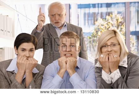 Angry boss shouting and pointing at scared employees in office.?