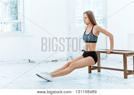Beautiful young slim woman doing push ups at the gym with orange dumbbells on white background