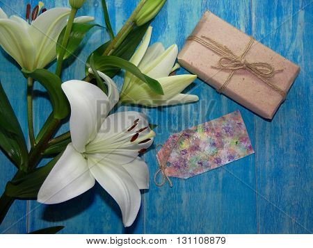 beautiful Lily flowers are on blue wooden boards, lying beside the paper for labels and gift