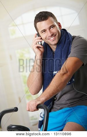 Man sitting on stationary bike after training and talking on mobile phone.