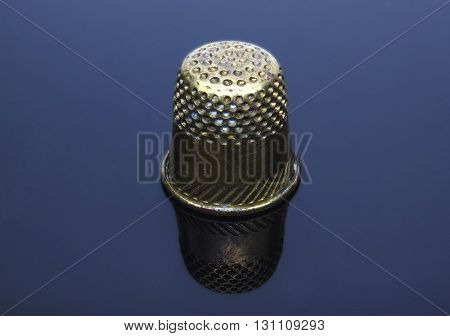 Old-time copper thimble on turn blue background with reflection