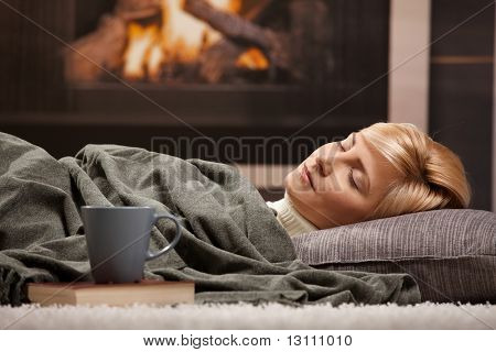Woman sleeping at home lying on floor in front of a fire place,