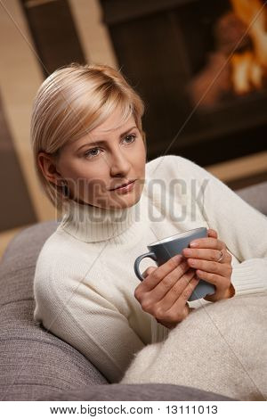 Woman sitting on sofa at home drinking hot tea, looking away.