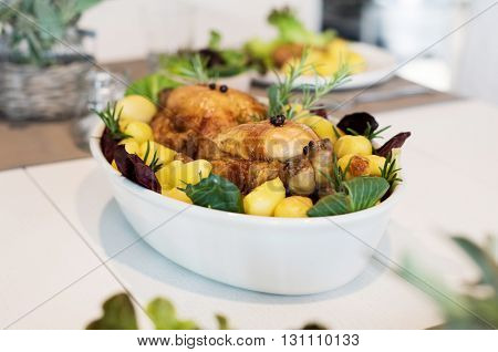 Two whole grilled chickens with herbs, rosemary and baked potatoes served in a pan on table. Closeup of roasted chickens made by chef in a restaurant. Healthy meal served for lunch.