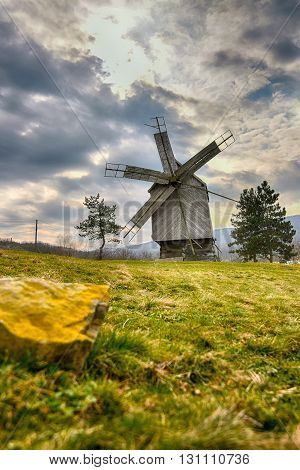 Wood windmill with grass and dramatic sky