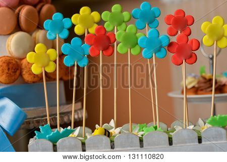 Flower lollipops with different colors and rustic background