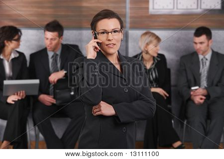 Portrait of happy businesswoman standing in office lobby, talking on mobile phone, smiling.?