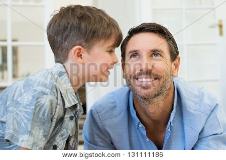 Son tell a secret at ear to his father. Happy child whispers a secret to her daddy. Portrait of smiling dad and son playing at home. Happy child whispers a secret to her daddy.