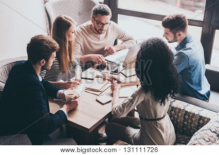 Pay attention to this! Young handsome man pointing at digital tablet while sitting at the office table on business meeting with his coworkers