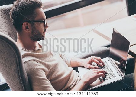 Working with pleasure. Side view of handsome man using his laptop while sitting in chair in front of window