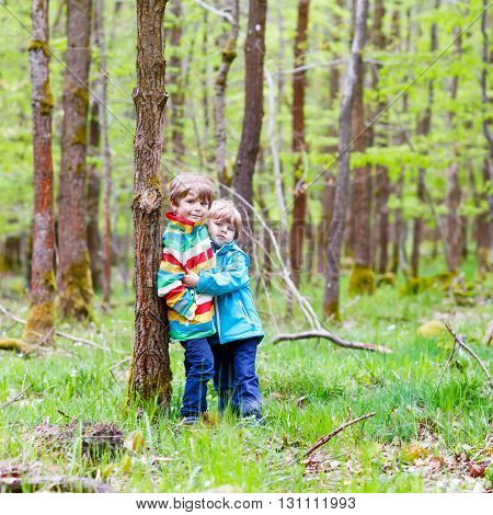 Two little cute smiling kid boys in bright jackets walking together in a forest on a rainy day. Friendship between siblings. Happy family, carefree childhood, brother love concept