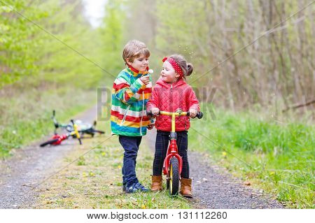 Little girl and boy playing together in forest in bright jackets on a rainy day with bikes. Children blowing dandelion flowers. Friendship between siblings.