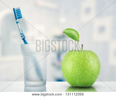 Toothbrush and green apple - caries prevention