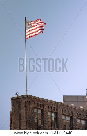 American flag on the house on a background of blue sky