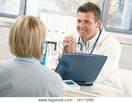 Smiling doctor talking to patient at office desk.