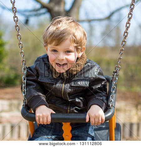 Happy little kid boy having fun on chain swing. Toddler child smiling and laughing on playground on spring day.