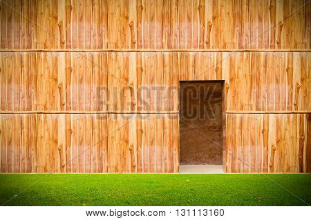 wooden wall with door and grass floor in front off